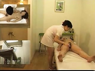 Cute Japanese babe has a of a female lesbian masseuse fingering her cunt